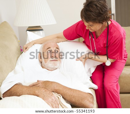Home health nurse fluffs an elderly patient's pillow. - stock photo