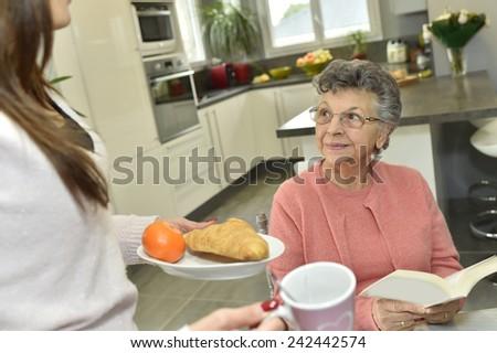 Home helper serving breakfast to elderly woman - stock photo