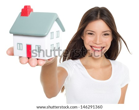 Home / house. Buying new home concept - woman holding mini house. House mortgage and happy home owner conceptual image with multi-ethnic Asian Chinese / Caucasian female model on white background. - stock photo
