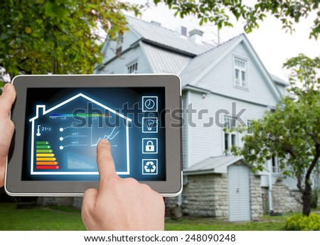 home, housing, people and technology concept - close up of man hands pointing finger to tablet pc computer and regulating room temperature over house background - stock photo