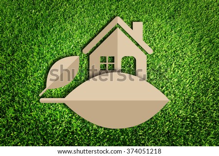 Home icon. Paper cut of eco on green grass. - stock photo
