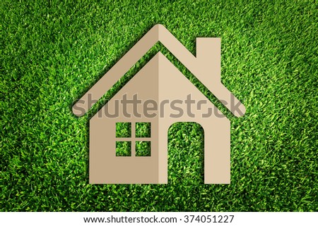 Home icon. Paper cut of eco on green grass.