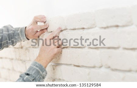 Home improvement, close up of a specialist installing decorative brick tiles with shallow depth of field and copy space - stock photo