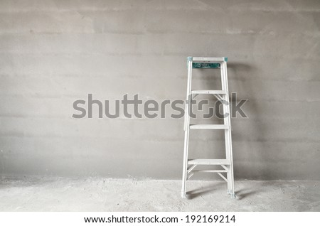 Home improvement concept with ladder and plaster wall - stock photo
