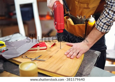 Home improvement - handyman drilling wood in workshop - stock photo