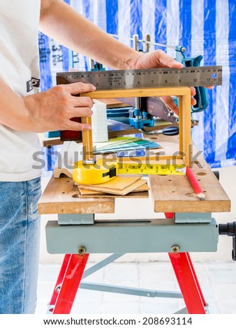 Home improvement - handyman measuring wooden frame  with woodworking tools in workshop - stock photo