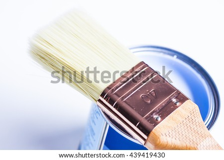 Home improvement paint brush and opened can of blue paint - stock photo