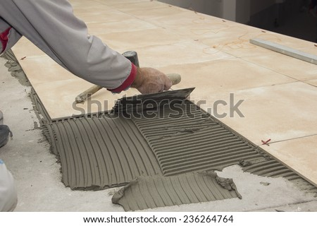 Home improvement, renovation - construction worker tiler is tiling, ceramic tile floor adhesive, trowel with mortar - stock photo