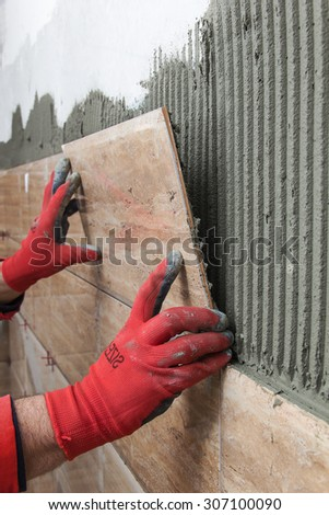 Home improvement, renovation - construction worker tiler is tiling, ceramic tile wall adhesive - stock photo