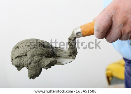 Home improvement, renovation - Hand holding a bucket trowel with cement mortar in construction site - stock photo