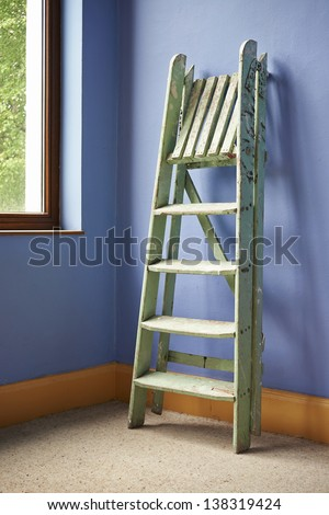 Home improvement with ladder and blue wall - stock photo