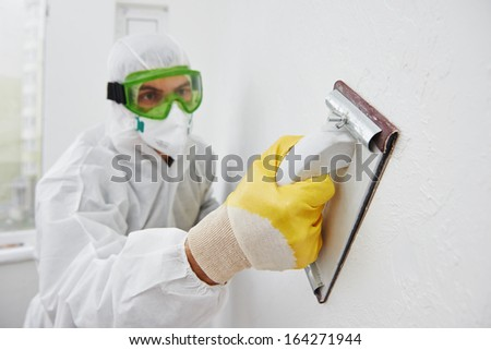 Home improvement worker in protective mask and glasses working with sander for smoothing wall surface - stock photo