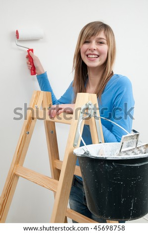Home improvement. Young woman painting wall with paint roller - stock photo