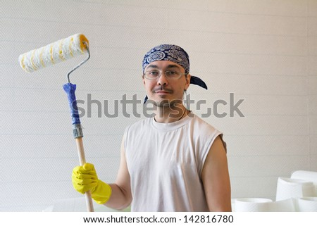 Home improvement. Young worker holding painting roller - stock photo