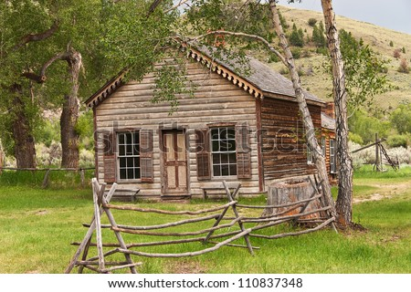 Home in Bannack State Park in Montana with fancy trim and shutters - stock photo