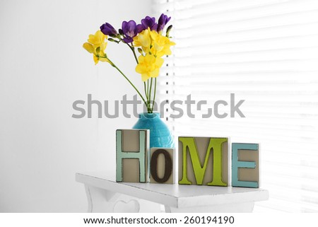 Home in colorful letters and spring flowers in light white interior - stock photo