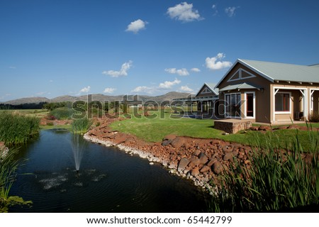 Home in lush countryside by stream with fountain - stock photo