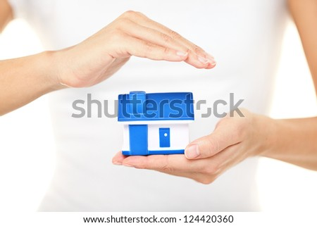 Home insurance. Woman holding a model house in one hand while forming a protective covering with the other conceptual of home insurance and protection - stock photo