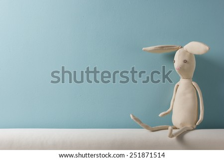 Home interior. Childhood. Blue background. Toy sitting on a couch. Copy space. - stock photo