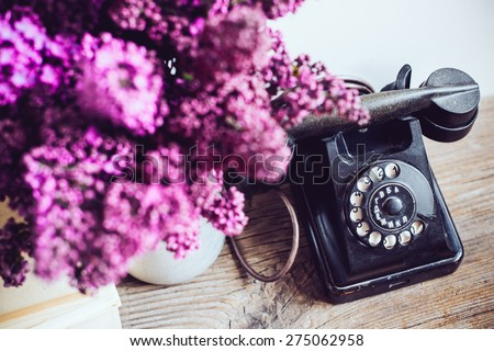 Home interior decor, bouquet of lilacs in a vase, a vintage rotary phone and books on rustic wooden table, on a white wall background - stock photo