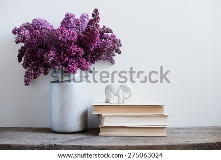 Home interior decor, bouquet of lilacs in a vase and books on rustic wooden table, on a white wall background