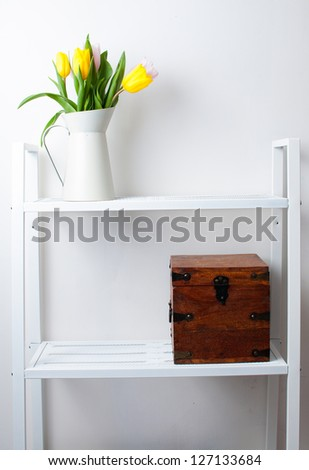 home interior decoration: a bouquet of tulips in a jug and a wooden box on white shelves - stock photo