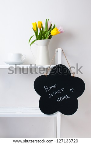 home interior decoration: a bouquet of tulips in a jug, cup and saucer, and chalk board on the white shelves - stock photo