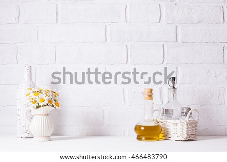Home interior decoration, bouquet of daisies in white vase, decorative white bottle and glass bottle of oil in a basket