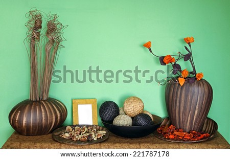 Home interior decorative objects in front of green wall - stock photo