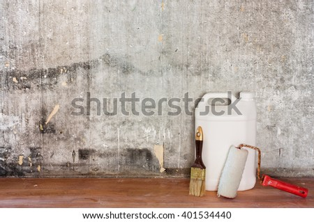 Home interior room repair concept - old gray concrete wall and dirty brown floor in repairing room with white plastic can, paint roller and brush near the wall, close-up view  - stock photo