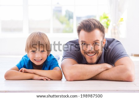 Home is where father is. Happy father and son leaning their faces on hands and smiling while lying on the floor at home  - stock photo