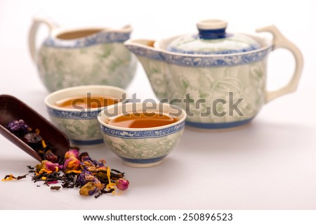 Home is where the tea is. Beautiful composition of Chinese traditional crockery teapot and cups surrounded by flowering tea isolated on white background with selective focus