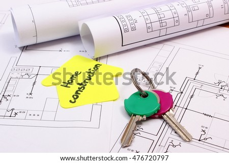 Home keys, house of yellow paper with text home construction and rolls of diagrams lying on electrical construction drawing of house, concept of building home