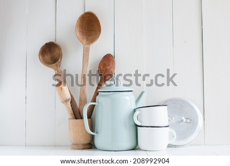 Home kitchen still life: Vintage coffee pot, enamel mugs and antique rustic wooden spoons on a barn wall background, soft pastel colors. - stock photo
