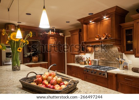 Home Kitchen with Island, Sink, Cabinets, Pendant Lights, Stove-top Range, and Hardwood Floors in New Luxury House - stock photo