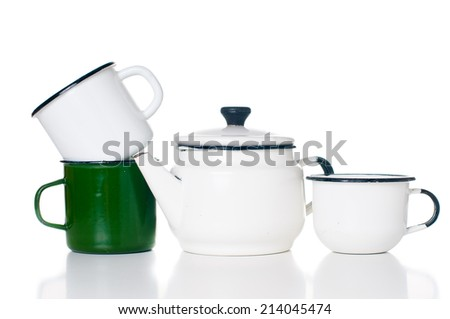 Home kitchenware, vintage enameled kettle and mugs isolated on white background
