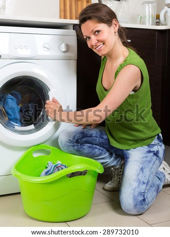 Home laundry. Attractive smiling girl using washing machine at home
