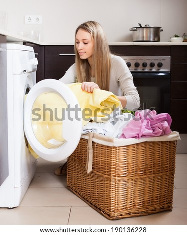 Home laundry. Blonde woman loading clothes into washing machine  in home - stock photo