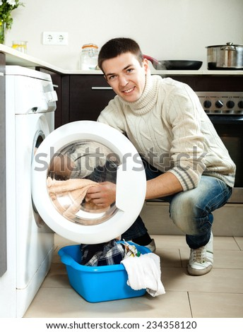 Home laundry. Handsome man loading clothes into the washing machine  in home