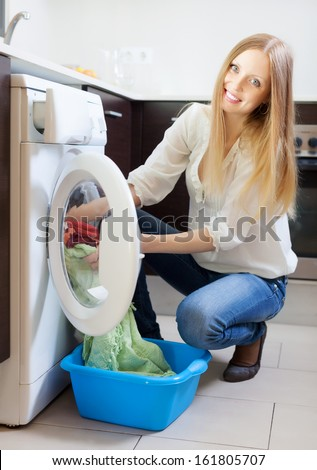 Home laundry. Happy blonde woman loading clothes into the washing machine