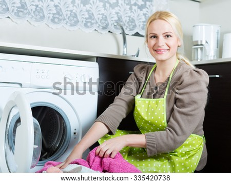 Home laundry. Happy blonde woman loading clothes into the washing machine in home  - stock photo