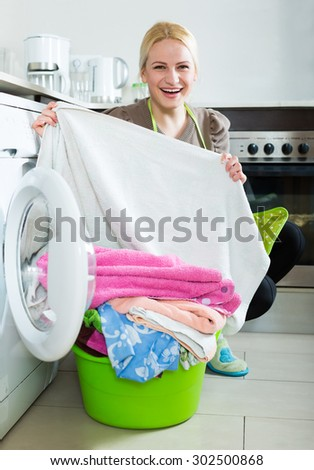 Home laundry. Happy blonde woman loading clothes into washing machine at the home