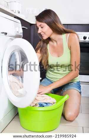 Home laundry. Happy young girl  loading clothes into washing machine  in home