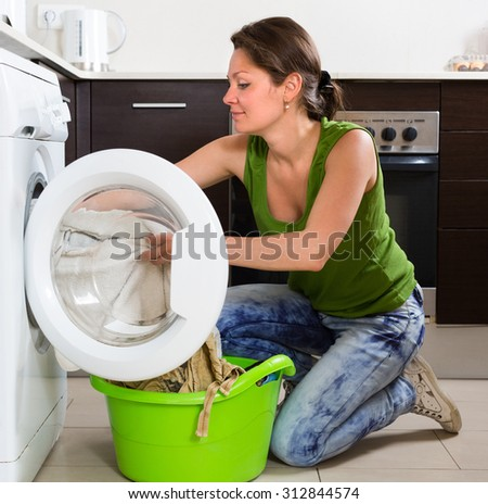 Home laundry. Smiling girl using washing machine at home  - stock photo