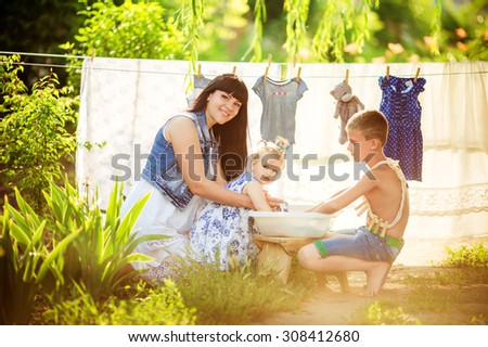 Home laundry. Smiling mother with little childrens using washing