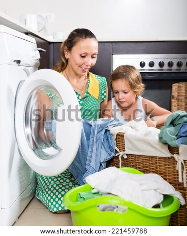 Home laundry. Smiling woman with child using washing machine at home. Focus on woman - stock photo