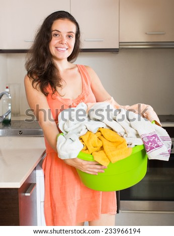 Home laundry. Smiling young housewife with linen basket near washing machine  - stock photo