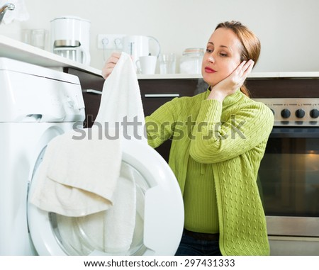 Home laundry. Tired woman in green using washing machine at home