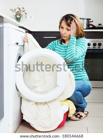 Home laundry. Unhappy  girl using washing machine at home