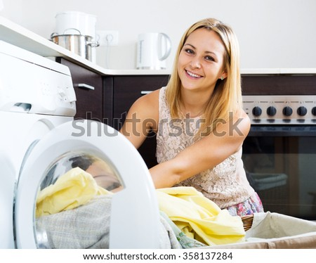 Home laundry.Young  blonde woman loading clothes into washing machine  in home - stock photo